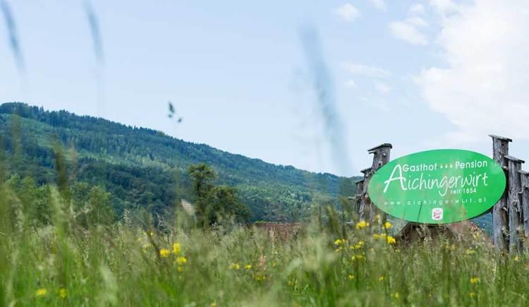 Blick auf das Schild und Logo vom Gasthof Aichingerwirt. Im Vordergrund eine Blumenwiese, im Hintergrund die Berge. (© Aichingerwirt)