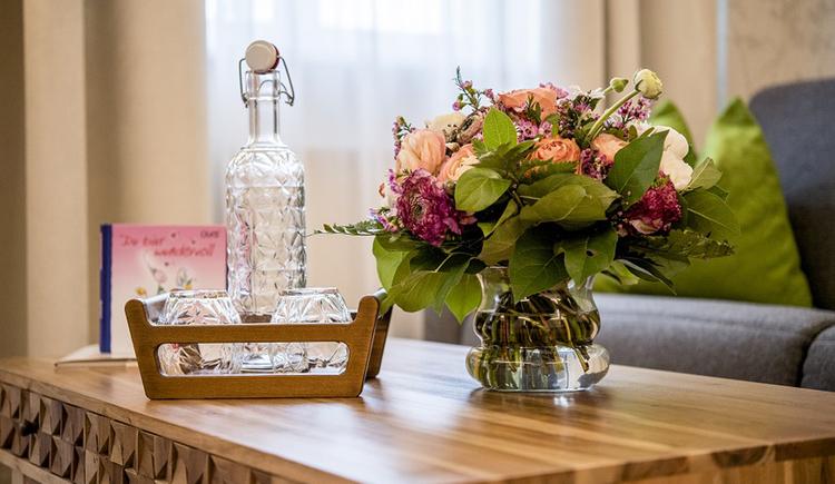 Glasflasche und Gläser auf einem Tisch, Blumenstrauß in einer Vase. (© Karin Lohberger)