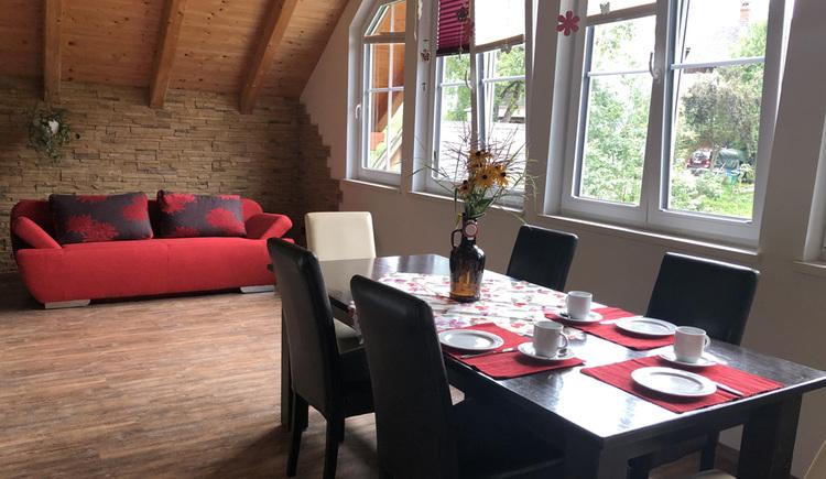 Offene Raumgestaltung mit Esszimmer, Couch und wunderschönen Panoramablick in die umliegende Bergwelt der Ferienregion Dachstein Salzkammergut.