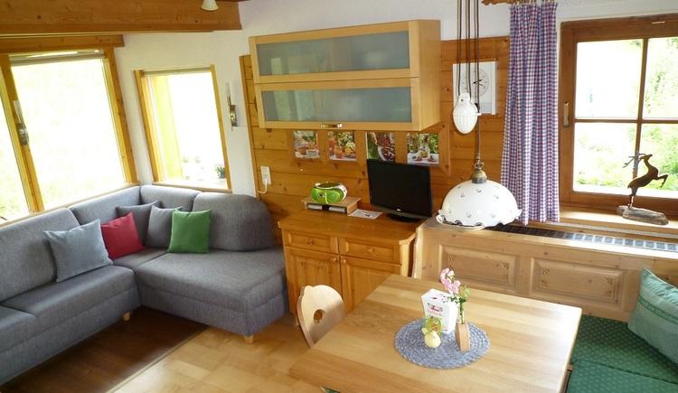 In der aufgrund der vielen Fenster sehr hellen Wohnstube der Unterkunft, sorgt die hochwertige Holzausstattung für eine angenehme Atmosphäre. (© Helga Hummelbrunner)