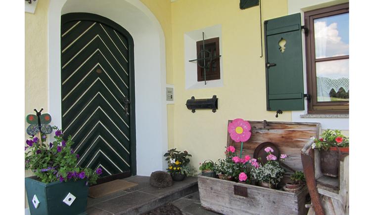 Hauseingang, im Vorderbereich verschiedene Blumen in Töpfe. (© Langwallner)