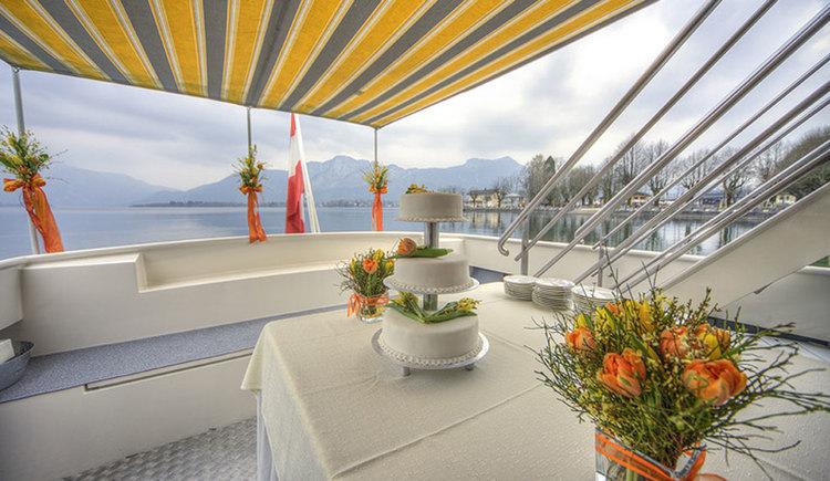 Hochzeitstorte am Schiff, das für eine Hochzeit dekoriert wurde, im Vordergrund Blumen, im Hintergrund Berge und See. (© Mondsee Schifffahrt Hemetsberger)