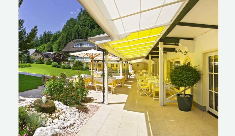 View to the terrace with chairs, tables under sunshades, sideways stones and shrubs, meadows, trees, houses. (© Hotel Seehof)