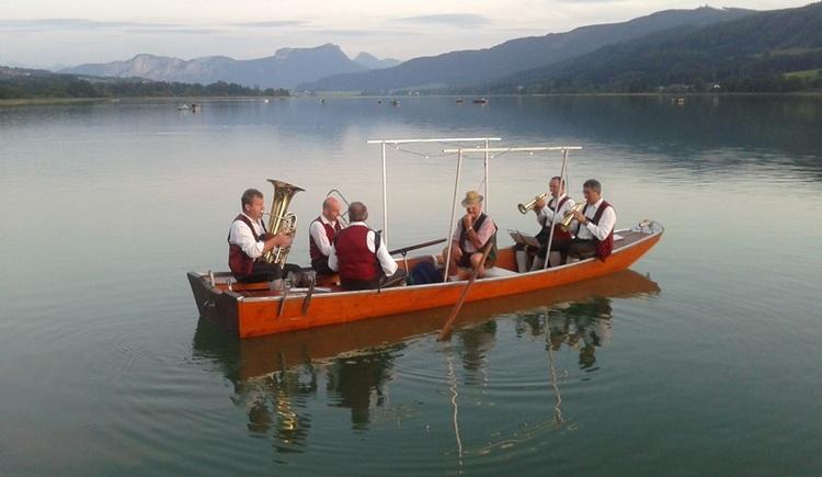 Personen auf einem Boot am See, im Hintergrund Berge