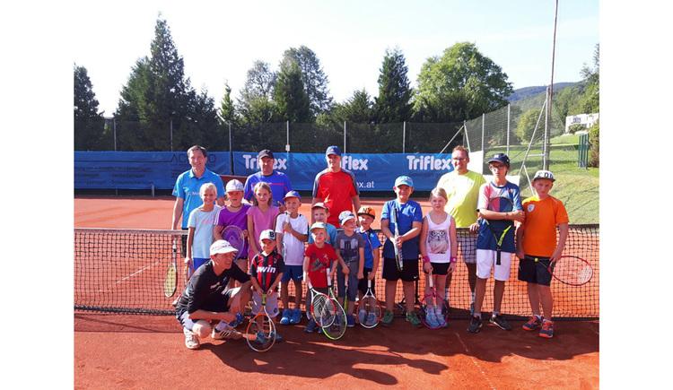 Personen - Kinder stehen auf einem Tennisplatz mit einem Tennisschläger in der Hand