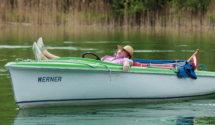 A man with hat is lying in an electro boat. (© Mondsee Schifffahrt Hemetsberger)