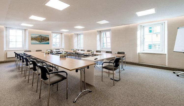 Seminarraum mit einigen Tischen, Stühlen und Flip-Chart