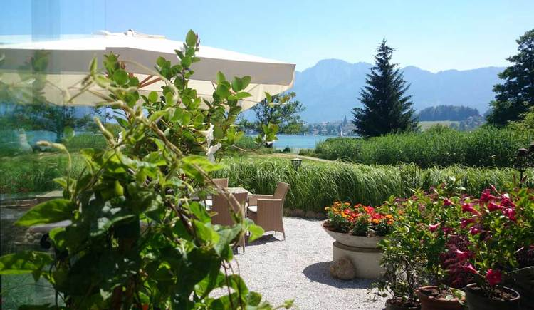 look from the terrace to the lake and the mountains, flowers, trees. (© Seehotel Lackner)