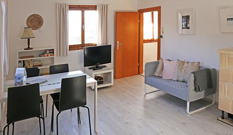 Wohnzimmer, mit Bank, Tisch und Stühle, TV, im Hintergrund ein Fenster