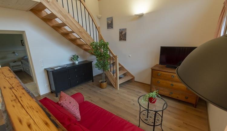 Den oberen Stockwerk mit Galerie, in dem sich das Bad und eines der Schlafzimmer befinden, erreichen Sie über eine Holzstiege.