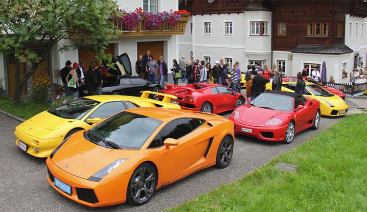 Autos und Personen stehen vor dem Haus, seitlich eine Wiese