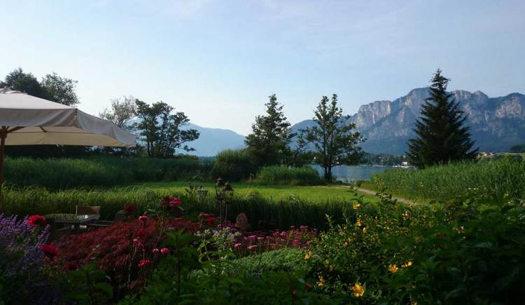 Look over the garden, flowers, sun shade, trees, lake and the Drachenwand. (© Seehotel Lackner)