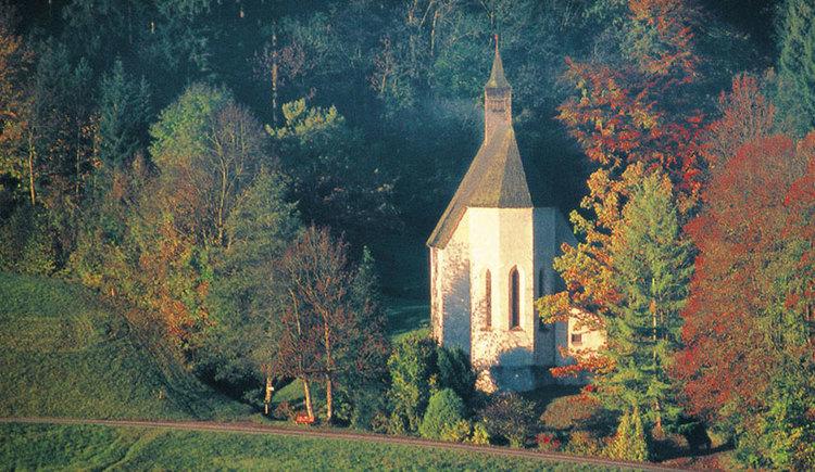 Blick auf die Konradkirche, umgeben von Wiese und Bäumen in herbstlichen Farben. (© www.mondsee.at)