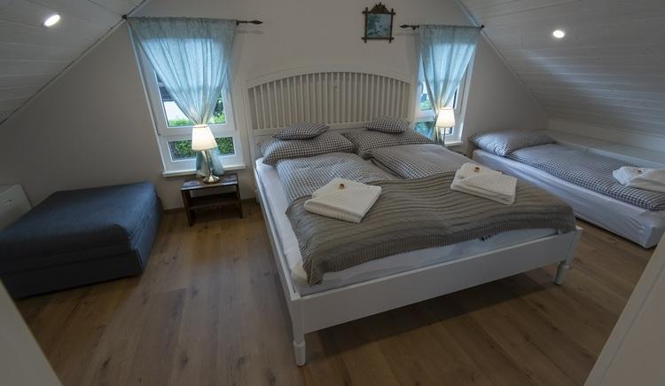 Das Schlafzimmer im Obergeschoss bietet Platz für insgesamt vier Personen. Es ist mit einem Doppelbett und zwei Einzelbetten ausgestattet.