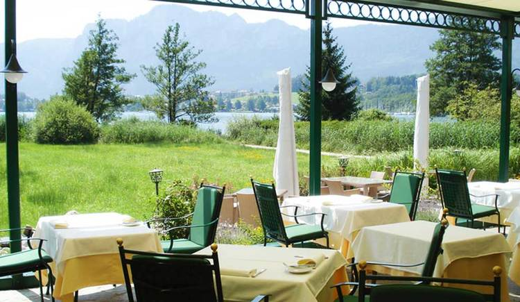terrace with tables and chairs, landscape with trees, Meadow, the lake, mountains. (© Seehotel Lackner)