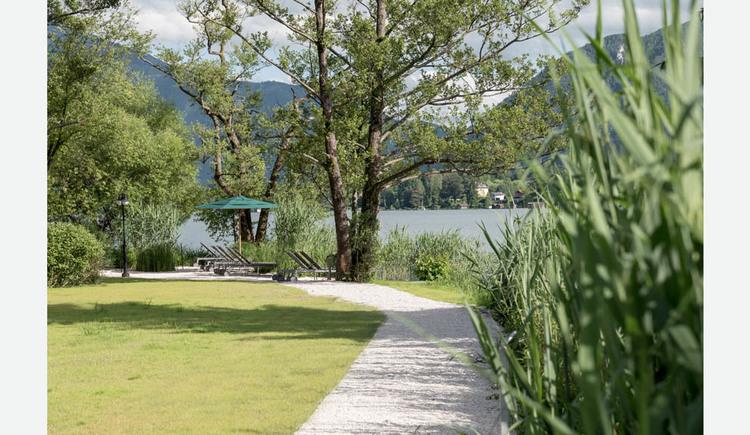 Weg zum Badeplatz, Liegestühle, Sonnenschirm, Bäume, Sträucher, im Hintergrund der See und die Berge. (© Lackner)
