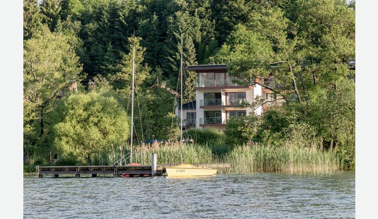 Blick vom See auf das Hotel, im Vordergrund ein Steg und ein Segelboot, Bäume. (© Lackner)
