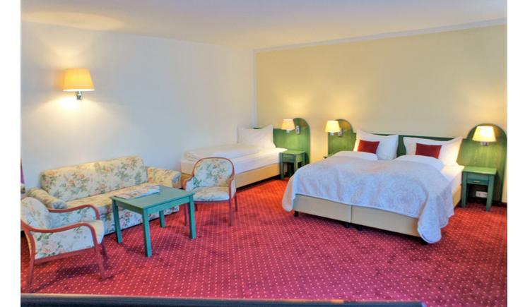 Doppelzimmer, mit Couch, Stühlen, Tisch, Zusatzbett. (© Hotel Villa Drachenwand)
