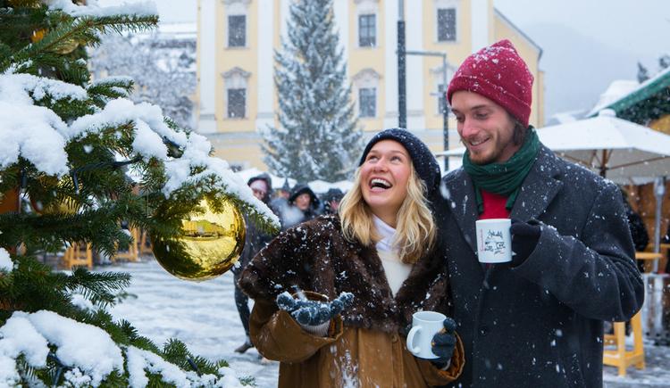Personen stehen mit einem Häferl vor einem Christbaum, im Hintergrund eine Kirche