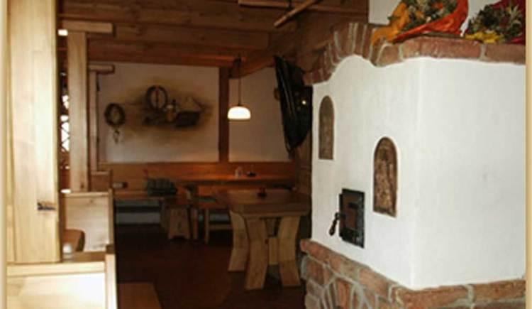 Innenbereich mit Tischen und Stühlen, und einen Ofen. (© www.mondsee.at)