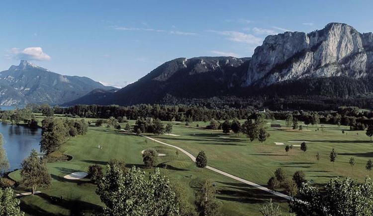 Blick auf die Wiese, Bäume, seitlich der See, im Hintergrund die Berge. (© Golfclub am Mondsee)
