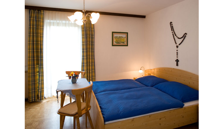 View into the room with double bed, small table with chairs, in the background a balcony door