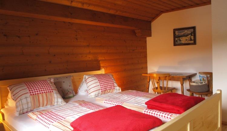 Rustikal mit viel Holz eingerichtetes Schlafzimmer mit Doppelbett. (© Pomberger)