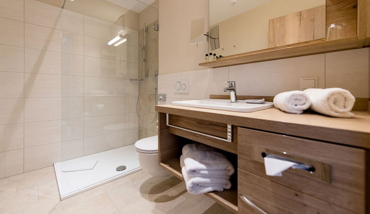 Waschbecken, Spiegel, im Hintergrund eine Dusche