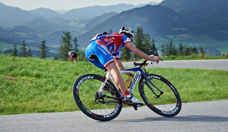 Radrennfahrer auf der Straße, im Hintergrund die Berge. (© Marco Felgenhauer)