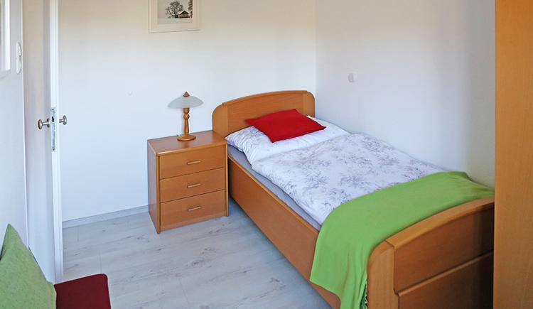Einzelbett, Nachtkästchen mit einer Lampe