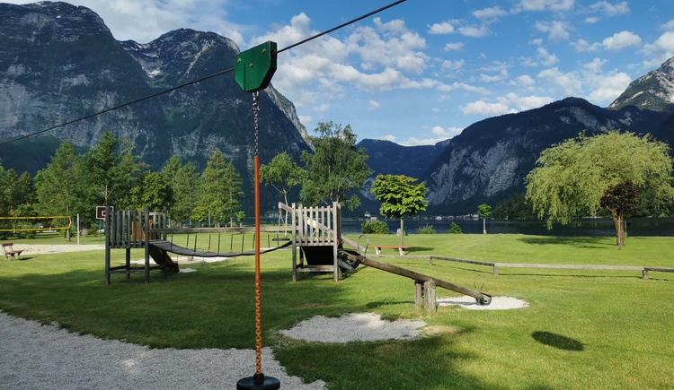 Ein Highlight am Spielplatz ist die Mini-Zipline, direkt am Hallstättersee. Im Hintergrund sieht man die beeindruckende Bergkulisse. (© Ferienregion Dachstein Salzkammergut)