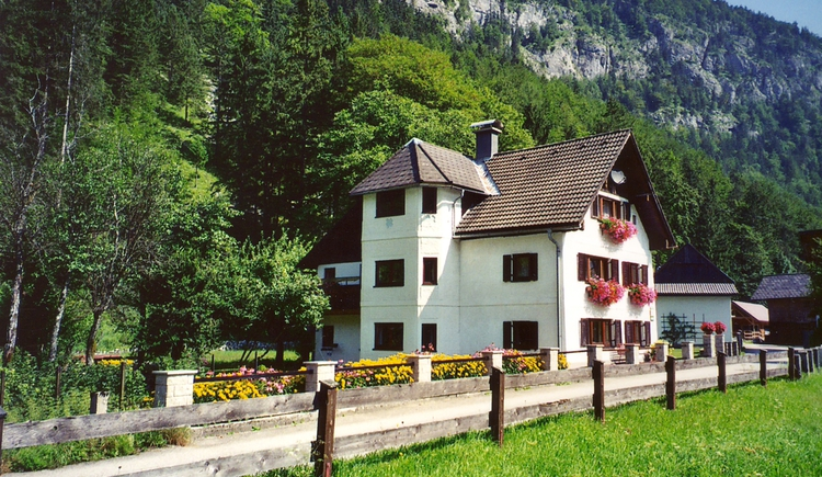 Das Bild zeigt das Haus Sulzbacher mit wunderschönem Blumenschmuck und der beeindruckenden Bergkulisse im Hintergrund. (© Haus Sulzbacher)