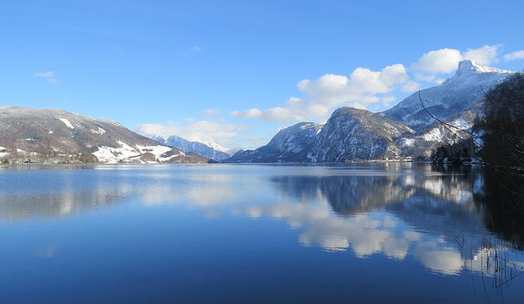 Ein winterlicher Blick über das Südostende des Mondsees. Rechts der schneebedeckte Schafberg, davor die Kienbergwand, rechts das Hochplettmassiv. Alle Berge spiegeln sich in der dominierenden glatten Wasseroberfläche. (© www.mondsee.at)