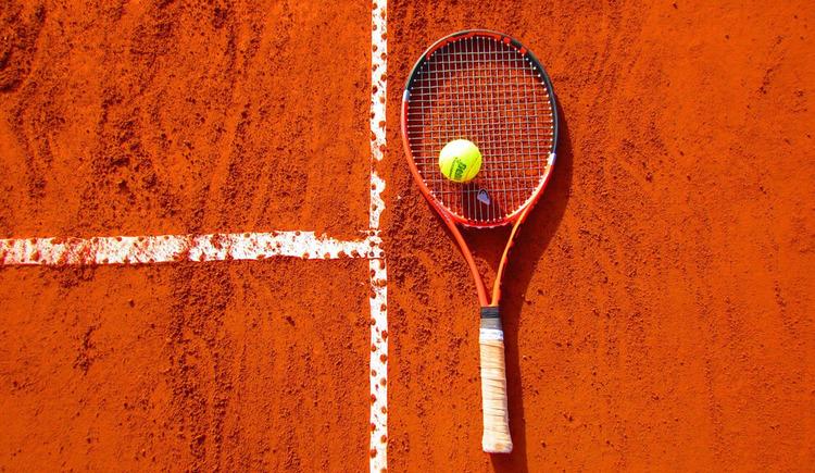Tennisschlaeger mit Ball auf Sandplatz. (© Bild von Cynthiamcastro auf Pixabay)