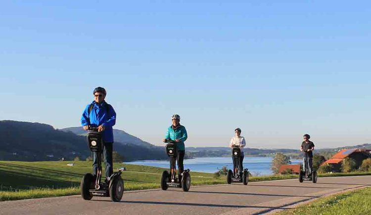 People are crossing a bridge with Segways
