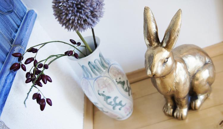 Hier sieht man einen Deko-Hasen und eine Blumenvase.