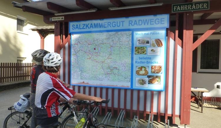 Radfahrer vor der Uebersichtstafel der Salzkammergut Radwege. (© Rosslwirt)