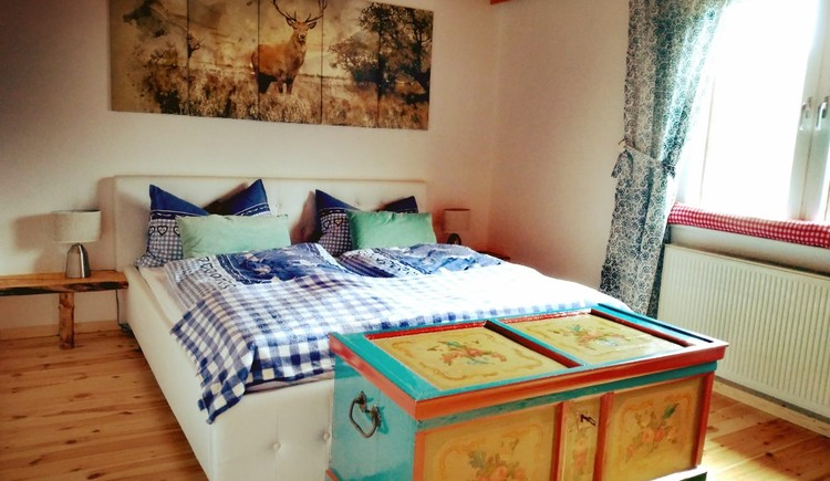 Bright bedroom with double bed, wooden floor and chest