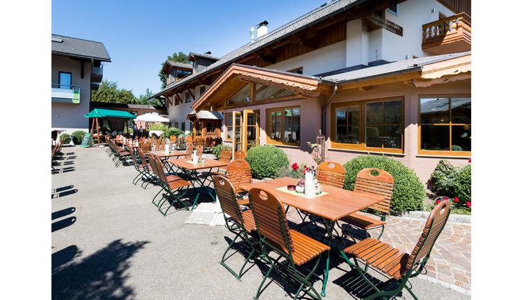 Gastgarten mit Tischen und Stühlen, im Hintergrund das Haus. (© Ellmauer)
