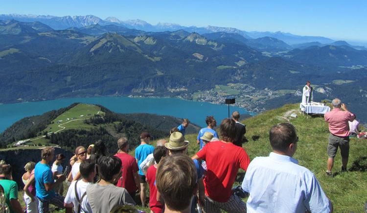 Personen am Berg, im Hintergrund der See und Berge