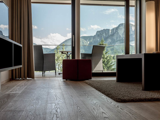 View from the living area with sideboard, TV, stool, table on the terrace with table and chairs, mountain views. (© Lackner)