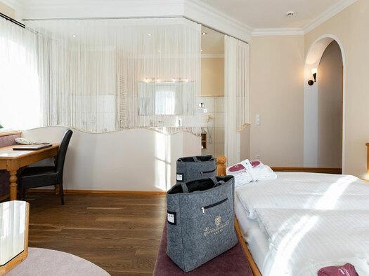 Blick zum Badezimmer, Doppelbett mit 2 grauen Taschen davor, Schreibtisch an der Wand mit Sessel, Leselampe darauf, kleiner Tisch mit Blumen und Flasche. (© Eichingerbauer)