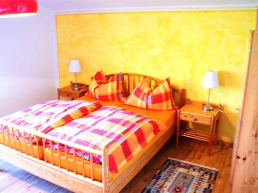 Schlafzimmer mit Doppelbett, Nachtkästchen mit Tischlampen. (© Riess)