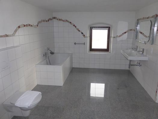 Badezimmer mit Badewanne, Waschbecken, Toilette, im Hintergrund ein Fenster. (© Taubenberger)