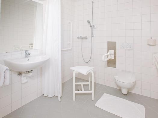 unterfahrbares Waschbecken, Dusche mit Haltegriffe und Sitzhocker, Haltegriffe bei der Toilette. (© Jugendgästehaus)