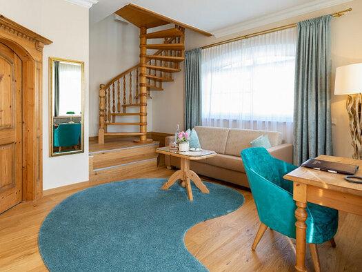 Holzboden mit großem Teppich, Wendeltreppe, Couch mit Tisch, Glasflasche und Blumen darauf, Schreibtisch mit Leselampe und Sessel. (© Eichingerbauer)