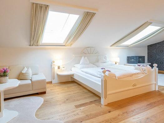 Couch mit Tisch darauf Flasche und Blumen, Bett mit Leselampe Teppiche auf Holzboden. (© Eichingerbauer)