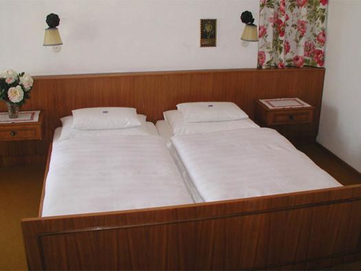 Schlafzimmer mit Doppelbett, Nachtkästchen, Lampen an der Wand. (© Knoblechner)