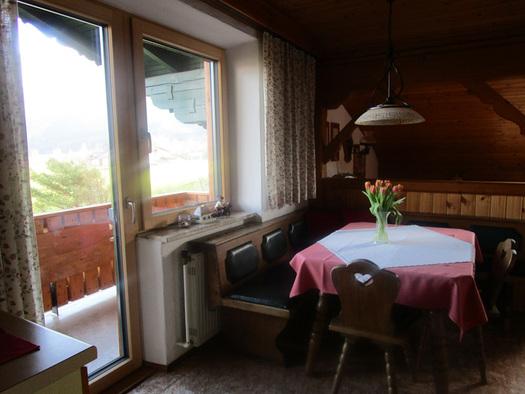 Essbereich mit Eckbank, Tisch und Stühle, Vase mit Blumen, seitlich Blick durch die Tür und das Fenster auf den Balkon. (© Familie Laireiter)
