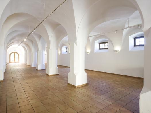 Halle mit Säulen, seitlich kleine Fenster. (© Schloss Mondsee)